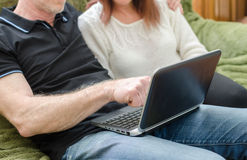 Couple sitting on a sofa using a computer Stock Image