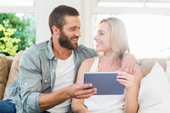 Couple sitting on sofa and using digital tablet Royalty Free Stock Image