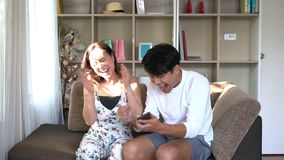 Couple sitting on sofa and very cheerful. Whale their looking the mobile