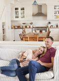 Couple Sitting On Sofa Watching Television Together stock photo
