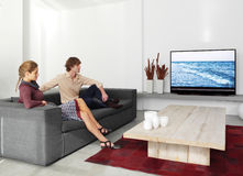 Couple sitting on the sofa watching tv ll. Young couple sitting on the sofa watching tv in the living room stock photo
