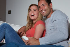 Couple Sitting On Sofa Watching TV Together. At Home Laughing Stock Image
