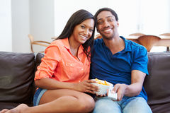 Couple Sitting On Sofa Watching TV Together Stock Photography