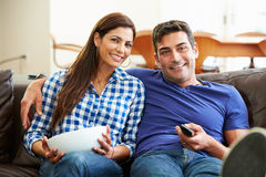 Couple Sitting On Sofa Watching TV Together. With Man Holding Remote Control Stock Images