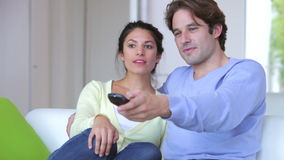 Couple Sitting On Sofa Watching TV Together. Couple sit on the sofa and playfully argue over who has the tv remote control.Shot on Canon 5d Mk2 with a frame rate stock footage