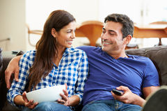 Couple Sitting On Sofa Watching TV Together. Smiling At Each Other Stock Photo