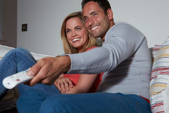 Couple Sitting On Sofa Watching TV Together. Using Remote Control Smiling Royalty Free Stock Photos