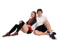 Couple sitting in sportswear on the floor stock photos