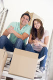 Couple sitting on staircase with boxes in new home Stock Images