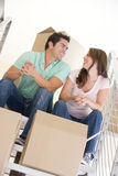 Couple sitting on staircase with boxes in new home Royalty Free Stock Images