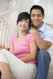 Couple sitting on staircase smiling. At camera Royalty Free Stock Image