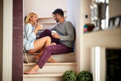 Couple sitting on stairs and drinking coffee stock photo