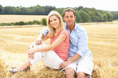 Couple Sitting On Straw Bales In Harvested Field Stock Photography