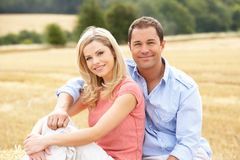 Couple Sitting On Straw Bales In Harvested Field Royalty Free Stock Photo