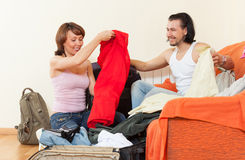 Couple sitting on a striped couch and packs a suitcase at home Royalty Free Stock Photography