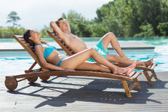 Couple sitting on sun loungers by swimming pool. Full length of a young couple sitting on sun loungers by swimming pool stock photos