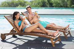 Couple sitting on sun loungers by swimming pool. Full length of a young couple sitting on sun loungers by swimming pool stock photo