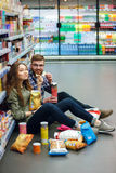 Couple sitting on the supermarket floor and eating snacks Royalty Free Stock Images