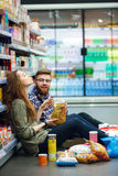 Couple sitting on the supermarket floor and eating snacks Royalty Free Stock Image