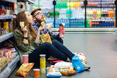 Couple sitting on the supermarket floor and eating snacks Stock Photos