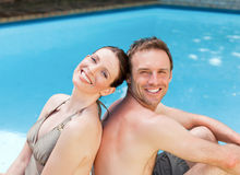 Couple sitting beside the swimming pool Stock Photography