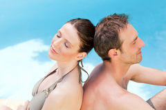 Couple sitting beside the swimming pool Stock Photo