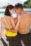 Couple sitting by swimming pool on a sunny day Royalty Free Stock Photography