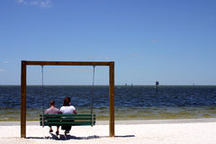 Couple sitting on a swing at the beach in Florida Royalty Free Stock Photos