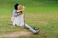 Couple sitting on a swing on their relaxing time in the garden. Thailand Stock Photography