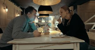 Man and woman having a talk in cafe. Couple sitting at the table in cafe and having a talk, woman drinking tea after finishing meals stock video footage