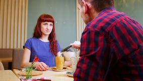 A couple sitting by table in a cafe. A man pours the drink in the cups stock video footage
