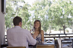 Couple sitting at table on restaurant balcony, raising wine glasses in toast, smiling Stock Photos