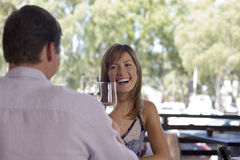 Couple sitting at table on restaurant balcony, raising wine glasses in toast, smiling Royalty Free Stock Photography