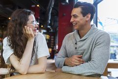 Couple sitting at table and talking in coffee shop stock photos