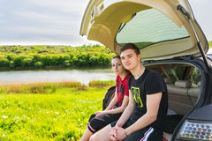 Couple Sitting on Tailgate of Car near River Stock Images