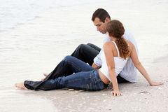 Couple sitting and talking in wet clothes at beach. Young couple at the beach in wet clothes sitting and talking Royalty Free Stock Photography
