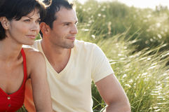 Couple Sitting In Tall Grass Stock Images