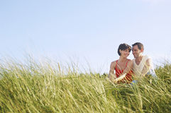 Couple Sitting In Tall Grass stock photos