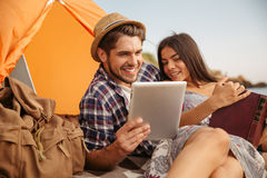 Couple sitting at tent using tablet computer and reading book Royalty Free Stock Photos