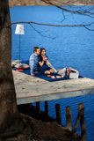 Couple sitting on terrace near blue water Stock Image