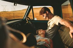 Couple enjoying on a road trip in their pick up truck. Couple sitting in their car enjoying the road trip in country side. Woman lying on the laps of the men Royalty Free Stock Photography