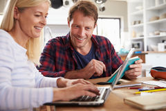 Couple sitting in their kitchen using laptop Stock Images