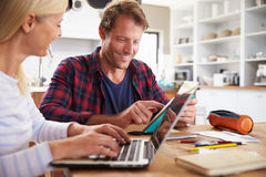 Couple sitting in their kitchen using laptop Royalty Free Stock Photo