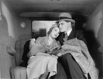 Couple sitting together on the back seat of a car Royalty Free Stock Images