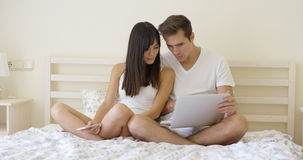 Couple sitting together in bed using computer Royalty Free Stock Image