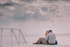 Couple sitting together by cloudy sea Stock Photography