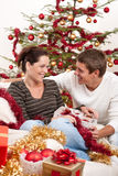 Couple sitting together in front of Christmas tree Royalty Free Stock Photo