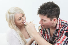 Couple sitting together at home, and eating sushi Stock Photos