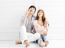 Couple sitting together and looking above. Young couple sitting together and looking above stock images