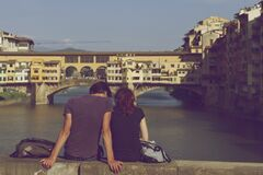 Couple Sitting Together near Ponte Vecchio Stock Photo